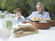 Grandfather And Grandson At Outdoor Table Stock Image