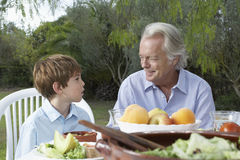 Grandfather And Grandson At Outdoor Table Stock Photo