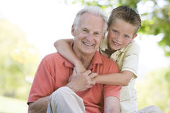 Grandfather and grandson outdoors smiling Royalty Free Stock Photography