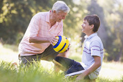 Grandfather and grandson at a park with a ball Stock Images