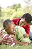 Grandfather And Grandson In Park With Football Stock Image