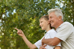 Grandfather and grandson  in park. Happy grandfather and grandson  in park. boy pointing with finger Stock Image