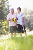 Grandfather and grandson at a park holding a ball Stock Photos