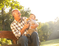 Grandfather with grandson in park Stock Photo