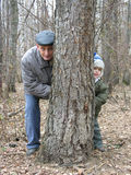 Grandfather and grandson play hide-and-seek. In park stock photos