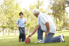 Grandfather And Grandson Playing American Football. In The Park Royalty Free Stock Image