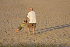 Grandfather and grandson playing on the beach Stock Images