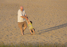 Grandfather and grandson playing on beach Stock Photos