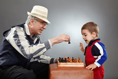 Grandfather and grandson playing chess Stock Photos