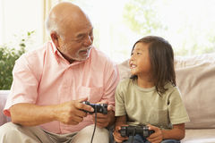 Grandfather And Grandson Playing Computer Game At Royalty Free Stock Photography