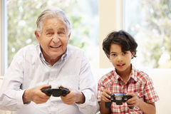 Grandfather and grandson playing computer games Stock Photos