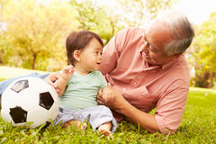 Grandfather And Grandson Playing With Football In Park Royalty Free Stock Photo