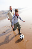 Grandfather And Grandson Playing Football On Winter Beach Royalty Free Stock Image