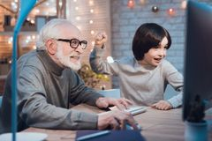 Grandfather and grandson are playing games on computer at night at home. Boy is cheering for granddad. stock image