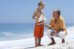 Grandfather and grandson (7-9) playing with toy boat on sandy beach, smiling Stock Images