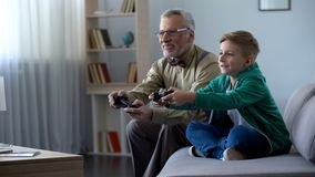 Grandfather and grandson playing video game with console, happy time together. Stock photo stock images
