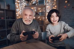 Grandfather and grandson are playing video games at night at home. Royalty Free Stock Photography