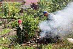Grandfather and grandson preparing barbecue Stock Photos