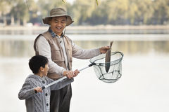 Grandfather and grandson putting fish into net at lake royalty free stock images