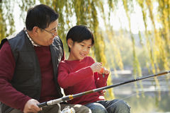 Grandfather and grandson putting lure on fishing line Royalty Free Stock Photography