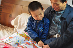 Grandfather and grandson reading Stock Photography