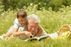 Grandfather and grandson reading book Stock Photography