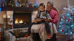 Grandfather and grandson reading a book stock video