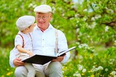 Grandfather with grandson reading book in spring garden Stock Photos