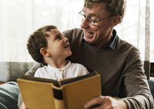 Grandfather and grandson reading a book together Stock Photos