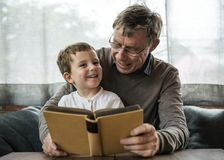 Grandfather and grandson reading a book together Stock Image