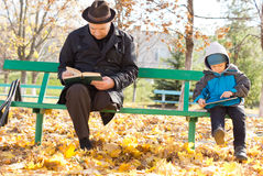Grandfather and grandson reading in the sun. Grandfather and grandson amusing themselves reading together in the autumn sunshine sitting on a park bench with the Stock Photo