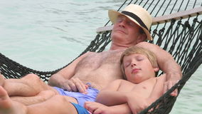 Grandfather And Grandson Relaxing In Beach Hammock. Grandfather and grandson lying in hammock with eyes closed.Shot on Canon 5d Mk2 with a frame rate of 30fps stock video footage