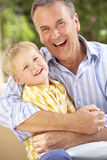 Grandfather And Grandson Relaxing On Sofa Together Stock Photos