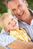 Grandfather And Grandson Relaxing On Sofa Together Stock Image