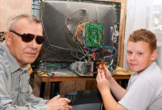 Grandfather and grandson. Are repairing an old TV Royalty Free Stock Photos
