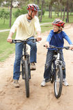Grandfather and grandson riding bicycle in park Royalty Free Stock Photos