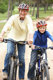 Grandfather and grandson riding bicycle in park Royalty Free Stock Photo