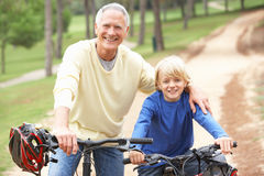 Grandfather and grandson riding bicycle in park Stock Photo