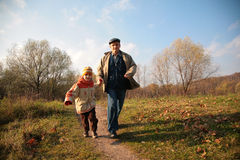 Grandfather and the grandson run on path royalty free stock photo
