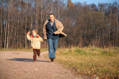 Grandfather and the grandson run on path Stock Image