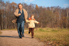 Grandfather and the grandson run on path Stock Photography