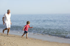 Grandfather And Grandson Running Along Beach Royalty Free Stock Images