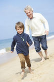 Grandfather And Grandson Running Along Beach Royalty Free Stock Image