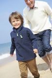 Grandfather And Grandson Running Along Beach Stock Photos