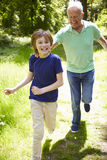 Grandfather With Grandson Running Through Countryside Royalty Free Stock Photo