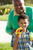 Grandfather And Grandson Shooting Water Pistols Stock Images