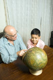 Grandfather and grandson sit on table with globe - Stock Photos