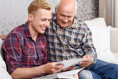 Grandfather and grandson sitting with album royalty free stock image