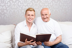 Grandfather and grandson sitting with album Stock Photography