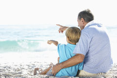 Grandfather And Grandson Sitting On Beach Together On Holiday Royalty Free Stock Image